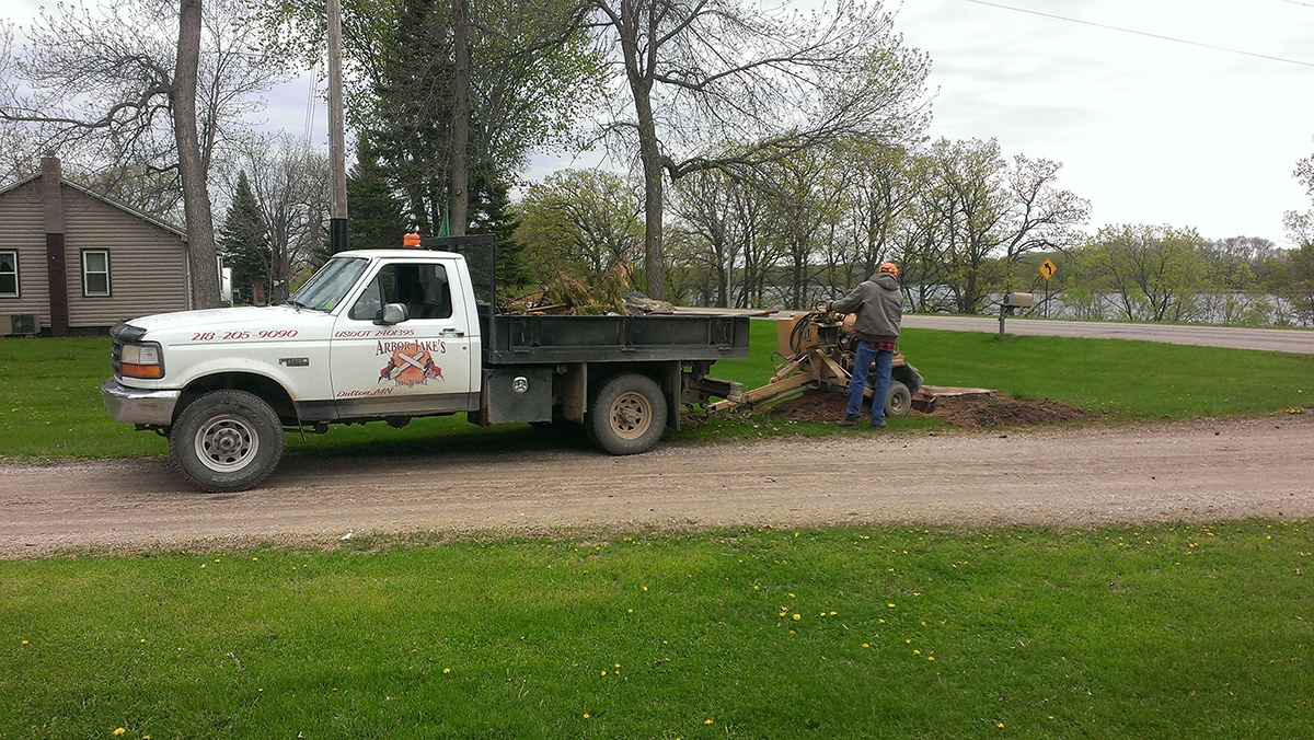 Arbor Jake's Tree Service truck with branches in back and crew member grinding stump